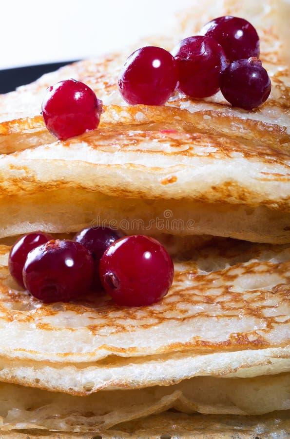 Pancake rubicondi su una banda nera con le bacche rosse di un mirtillo rosso fotografia stock