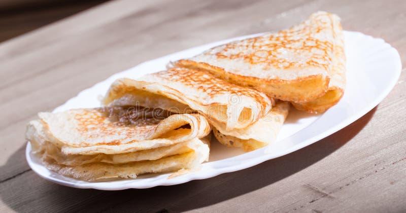 Pancake rubicondi sul piatto bianco che sta su una tavola da gray immagine stock libera da diritti