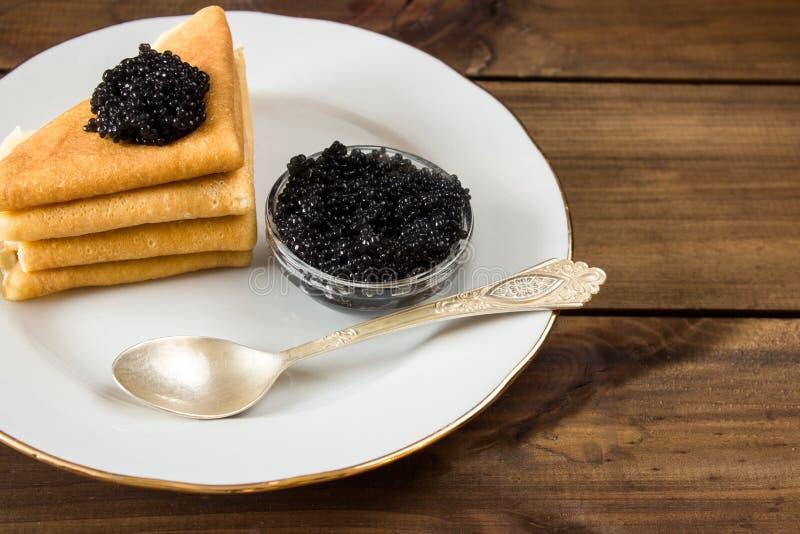 Pancake russi tradizionali sul piatto con il caviale nero fotografie stock libere da diritti