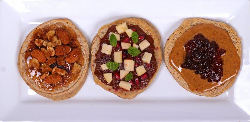 Pancake sani del grano intero con le guarnizioni fresche fotografia stock libera da diritti