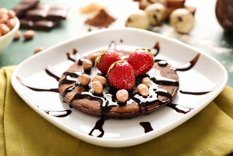 Pancake saporito del cioccolato con le arachidi e le fragole sul piatto fotografia stock libera da diritti