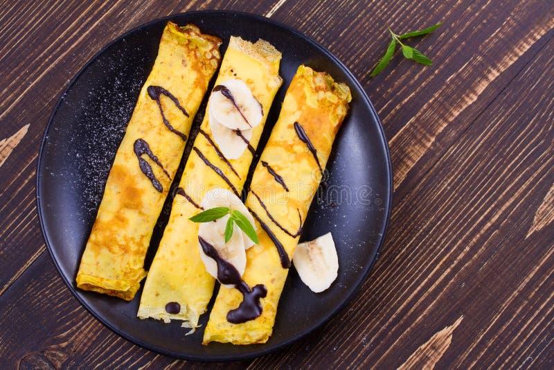 Pancake sottili avvolti con il riempimento, servito di banane fotografie stock libere da diritti