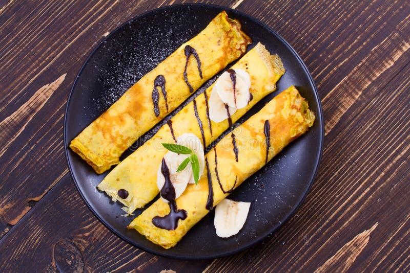 Pancake sottili avvolti con il riempimento, servito di banane immagine stock