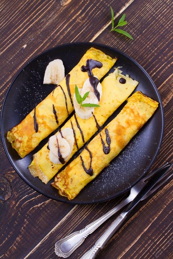 Pancake sottili avvolti con il riempimento, servito di banane immagini stock