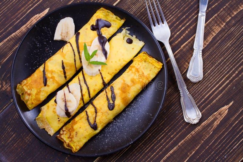 Pancake sottili avvolti con il riempimento, servito di banane fotografia stock