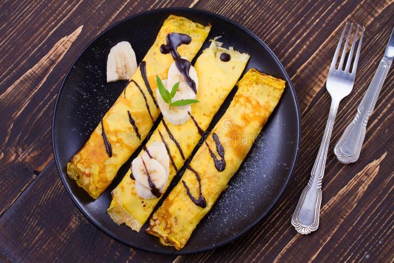 Pancake sottili avvolti con il riempimento, servito di banane fotografia stock libera da diritti