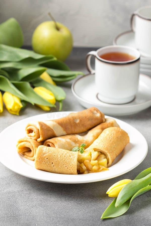 Pancake sottili (crêpe) con il ripieno di mele, rotoli farciti, alimento tradizionale russo per il maslenitsa, dessert francese,  fotografia stock libera da diritti