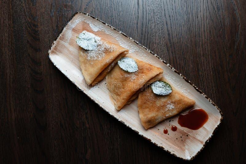 Pancake sottili dorati appetitosi con l'inceppamento di fragola dolce decorato con lo zucchero a velo su un piatto in un ristoran immagine stock libera da diritti