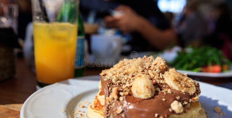 Pancake su un piatto bianco Vista del primo piano e fondo vago del caffè fotografia stock libera da diritti