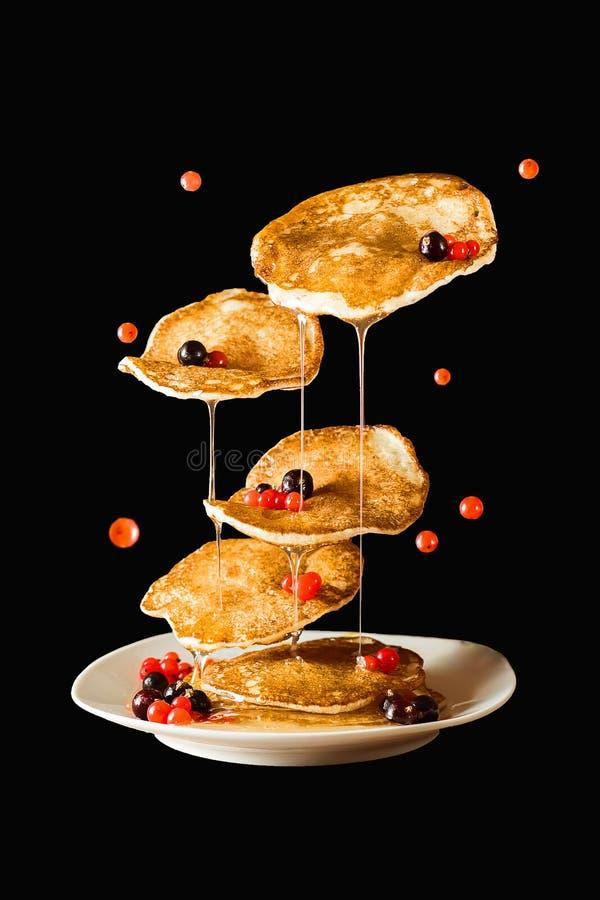 Pancake volanti con miele ed il ribes Priorità bassa nera immagini stock