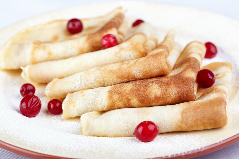 Pancakes. With cranberry berries on a white plate stock image