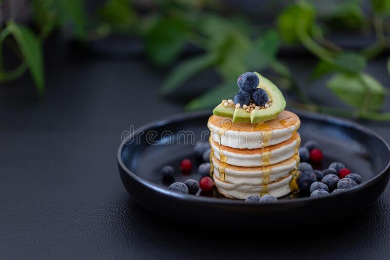 Pancakes with avocado and berries on top royalty free stock images