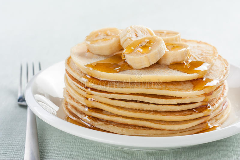 Pancakes with banana and syrup stock photos