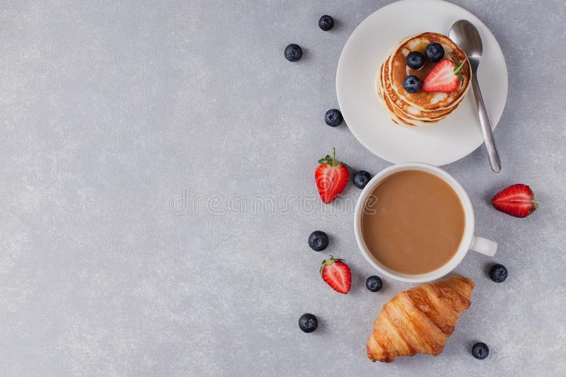 Pancakes with berries and a cup of fresh coffee on the right side, croissant, grey background royalty free stock image