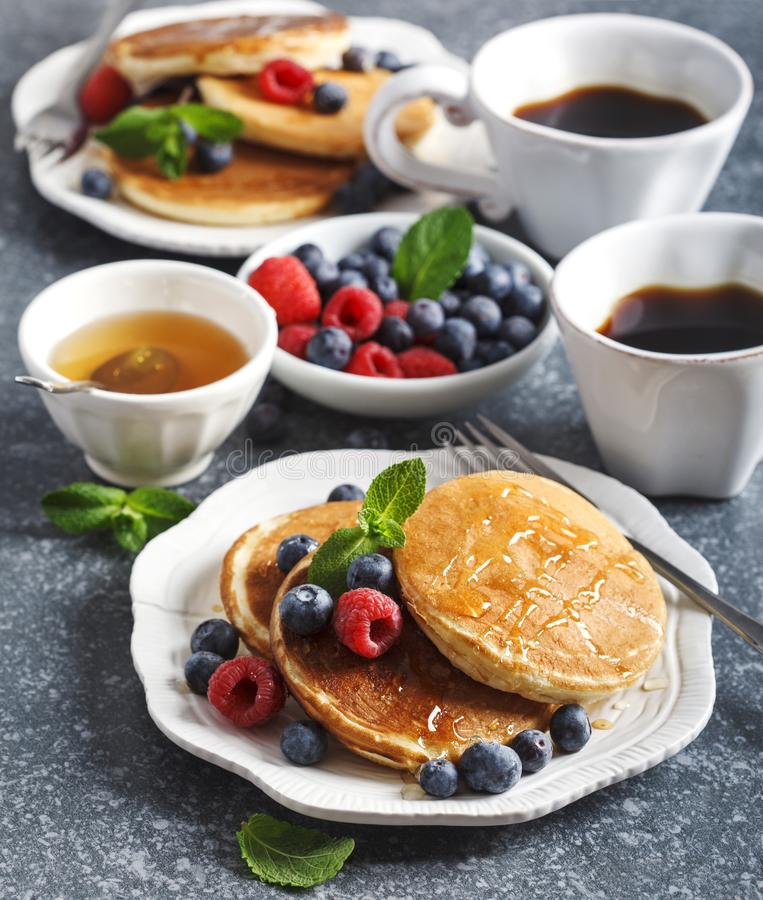 Pancakes with berries and honey stock photo