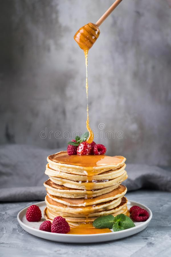 Pancakes with berries and honey stock images