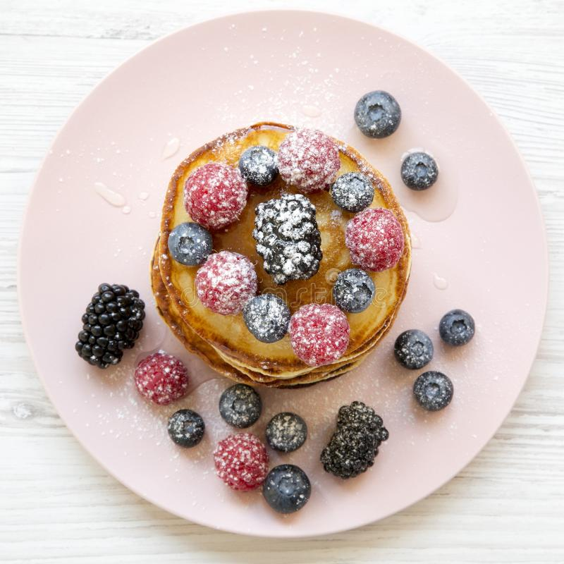 Pancakes with berries, honey and sugar on a pink plate on a white wooden table, overhead view. Flat lay, top view, from above. Clo. Se-up royalty free stock image