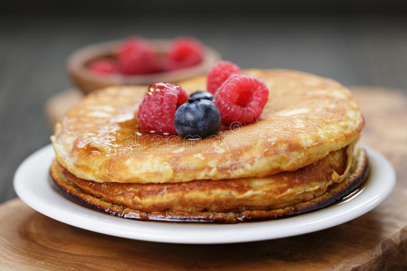 Pancakes with berries and maple syrup, on wooden table stock image