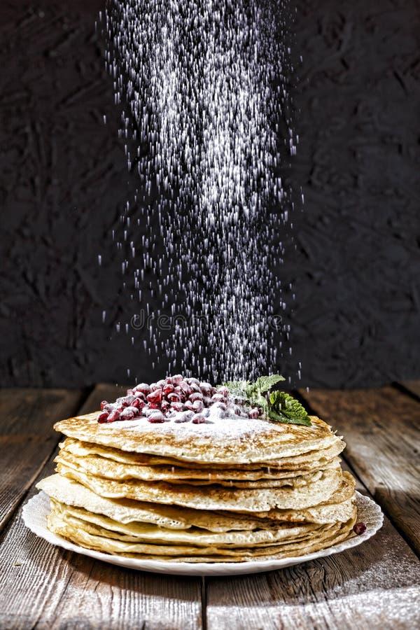 Pancakes, sprinkle, sugar powder, bakery, Maslennitsa, Mardi Gras, berries, mint leaves. Pancakes with berries, mint leaves and powdered sugar. Authentic bakery royalty free stock image