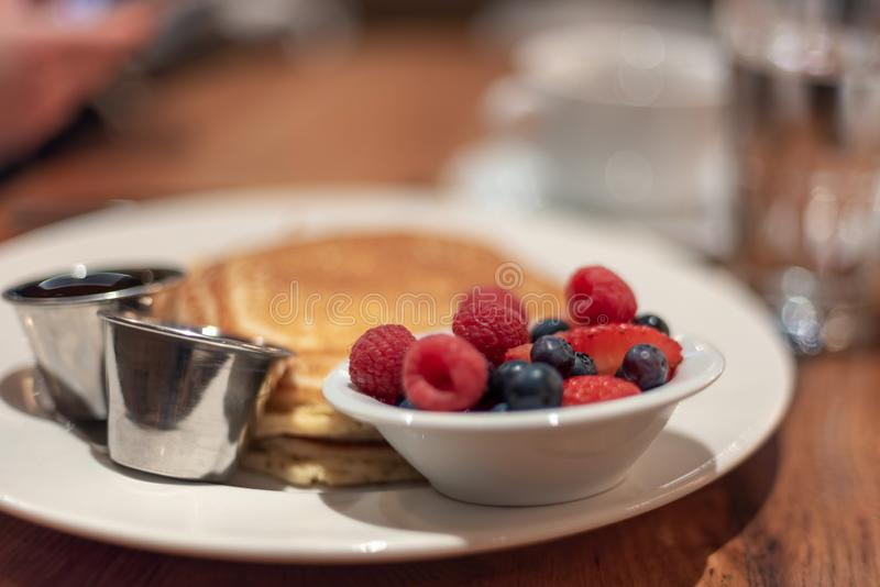 Pancakes with berries on the side. Breakfast food - pancakes,syrup and fresh berries stock photos