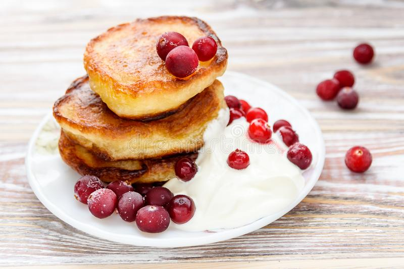Pancakes with berries and sour cream on a plate. Summer cottage of Russian delicacies stock photography