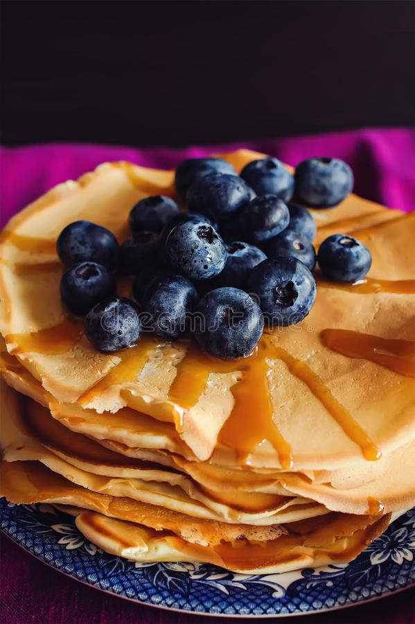 Pancakes with berries. Stack of pancakes with berries and caramel sauce on pink background royalty free stock photos