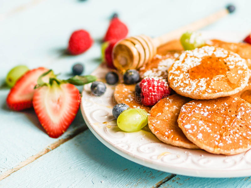 Pancakes with berries on wooden background royalty free stock image