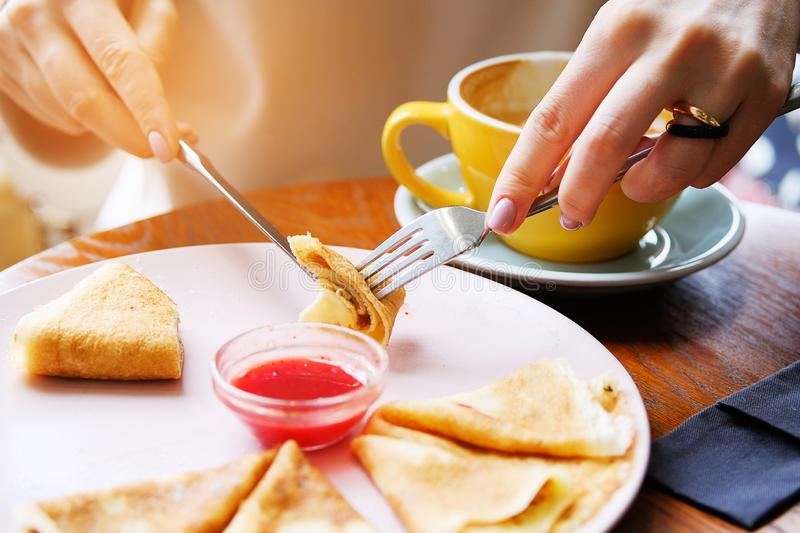 Pancakes with berry jam on a white plate on a wooden background close-up. Fork and knife in the hands of a woman. Next is a mug of royalty free stock image