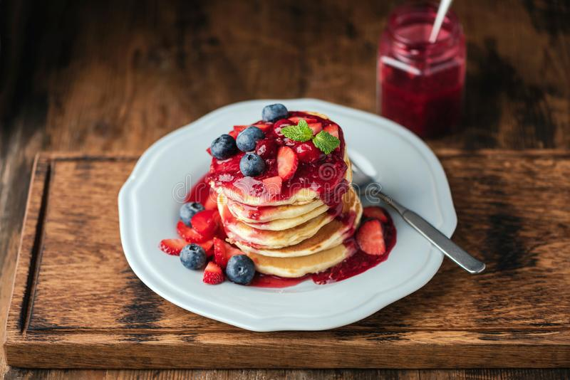 Pancakes with berry sauce and fresh berries royalty free stock photography