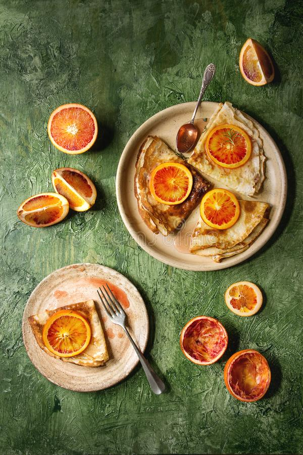 Pancakes with bloody oranges. Homemade crepes pancakes served in ceramic plates with bloody oranges and rosemary syrup with sliced sicilian red oranges over royalty free stock images