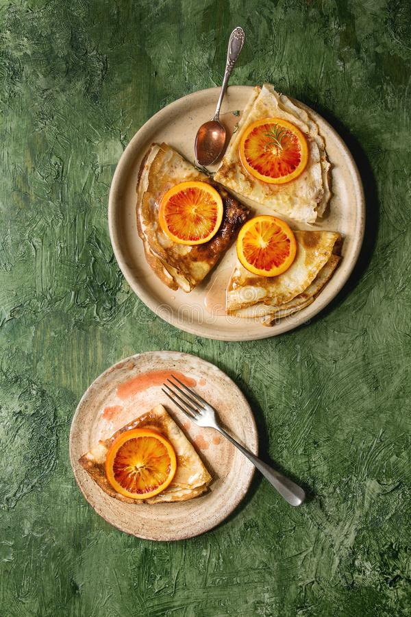 Pancakes with bloody oranges. Homemade crepes pancakes served in ceramic plates with bloody oranges and rosemary syrup with sliced sicilian red oranges over stock photography