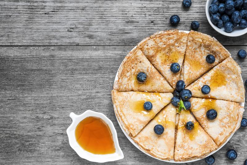 Pancakes with blueberries, maple syrup and mint leaf on top. Pile of thin homemade crepes with forest fruits. top view royalty free stock photos