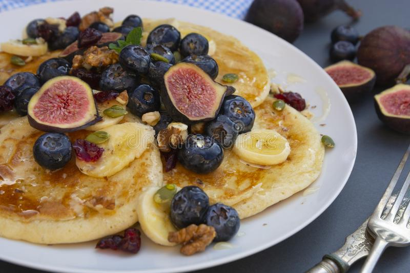Pancakes with blueberries, mint, fruits and honey for breakfast - homemade healthy food. Breakfast idea royalty free stock images