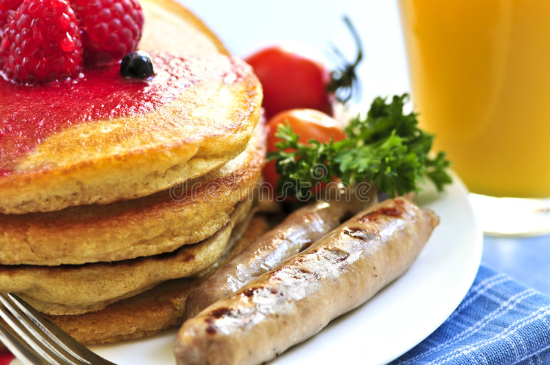 Pancakes breakfast. Breakfast of buttermilk pancakes with sausages and fresh berries royalty free stock image