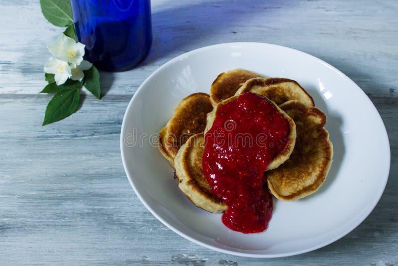 Pancakes for brekfast near beautiful white flowers. In blue bottle. jasmin. wooden grey background royalty free stock image