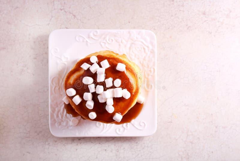 Pancakes with caramel sauce and marshmallow. On top stock photos