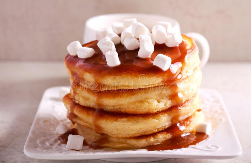 Pancakes with caramel sauce and marshmallow. On top stock photo