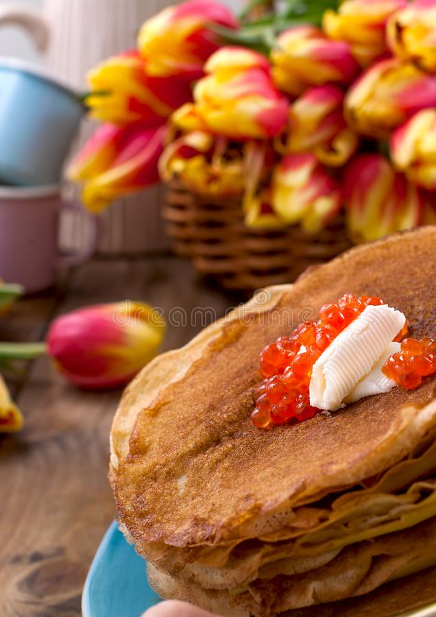Pancakes with caviar and butter, a bouquet of fresh tulips and a wooden background. Traditional Russian food for carnival. Top. View stock photo