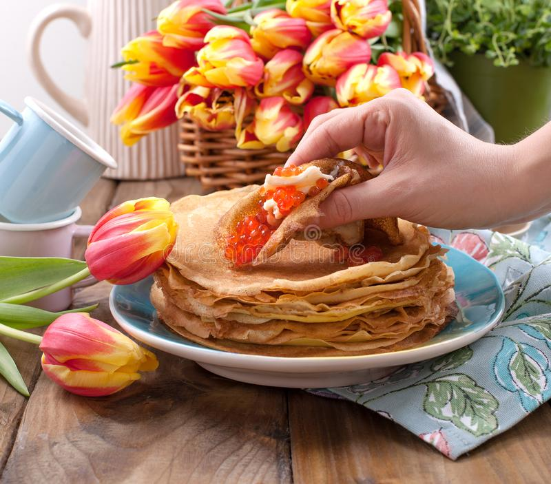 Pancakes with caviar and butter in a woman`s hand, a bouquet of fresh tulips and a wooden background. Traditional Russian food fo. R carnival royalty free stock images
