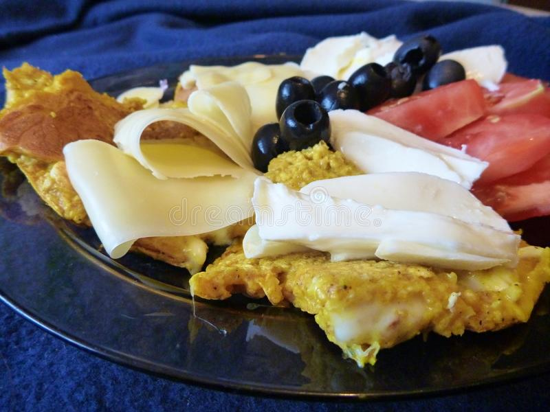 Pancakes with cheese olives and tomato. Served on a plate royalty free stock photos