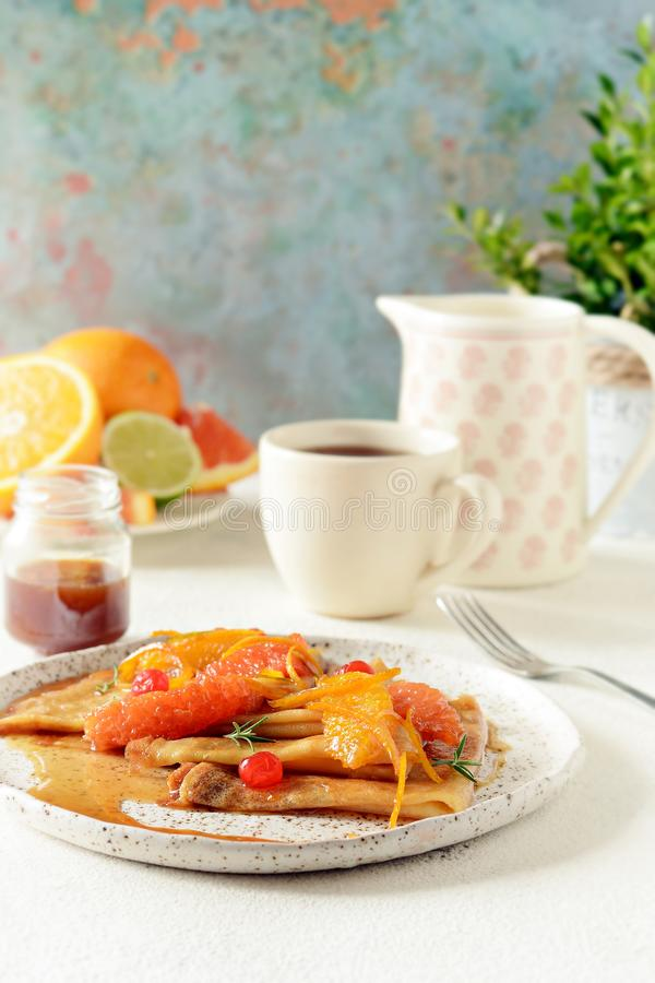 Pancakes crepe Suzette for breakfast with orange caramel sauce, orange slices, lime and orange zest and a cup of coffee. royalty free stock images