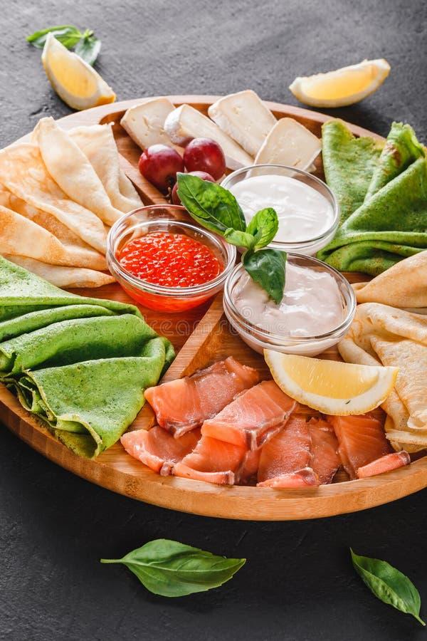 Pancakes or crepes with filet salmon, red fish caviar, sour cream sauce stock photos