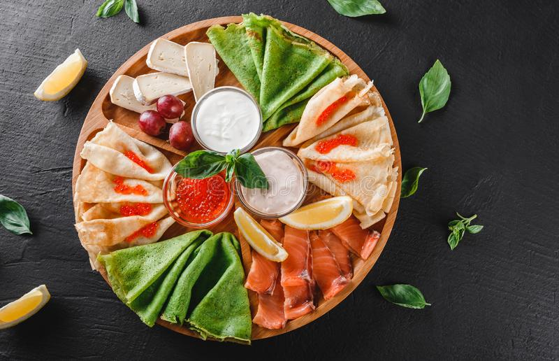 Pancakes or crepes with filet salmon, red fish caviar, sour cream sauce, cheese sauce on wooden board on dark background stock photo