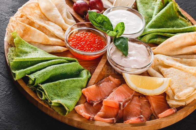 Pancakes or crepes with filet salmon, red fish caviar, sour cream sauce, cheese sauce on wooden board on dark background stock photos