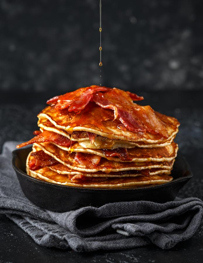 Pancakes with crispy bacon and maple syrup in cast iron skillet, frying pan. Morning Breakfast.  stock image