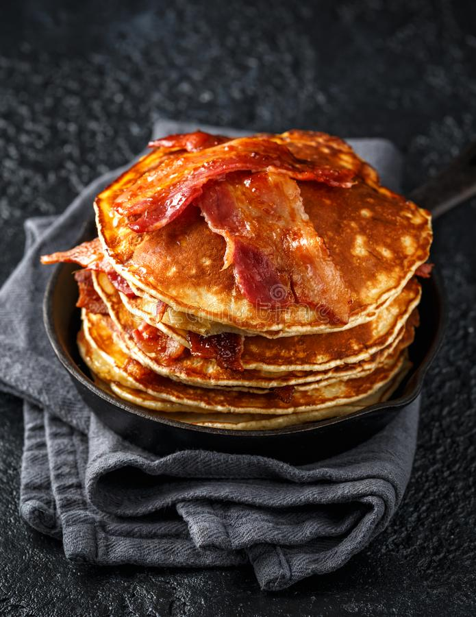 Pancakes with crispy bacon and maple syrup in cast iron skillet, frying pan. Morning Breakfast.  royalty free stock images