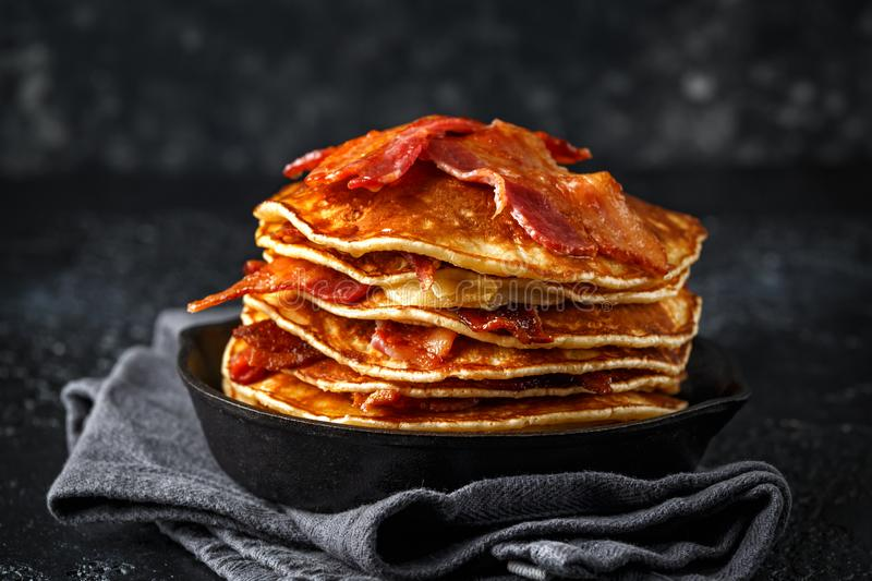 Pancakes with crispy bacon and maple syrup in cast iron skillet, frying pan. Morning Breakfast.  stock images