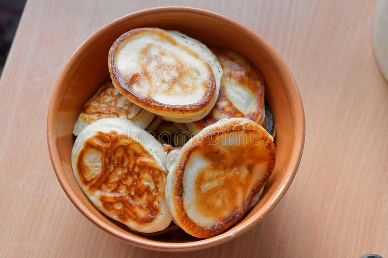 Pancakes in a deep bowl, fragrant pancakes in a plate, round small pancakes in a deep plate royalty free stock images