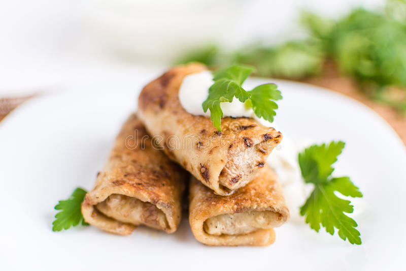 Pancakes filled with meat stuffing on a white plate. Delicious pancakes filled with meat stuffing on a white plate stock image