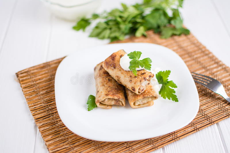 Pancakes filled with meat stuffing on a white plate. Delicious pancakes filled with meat stuffing on a white plate royalty free stock photos